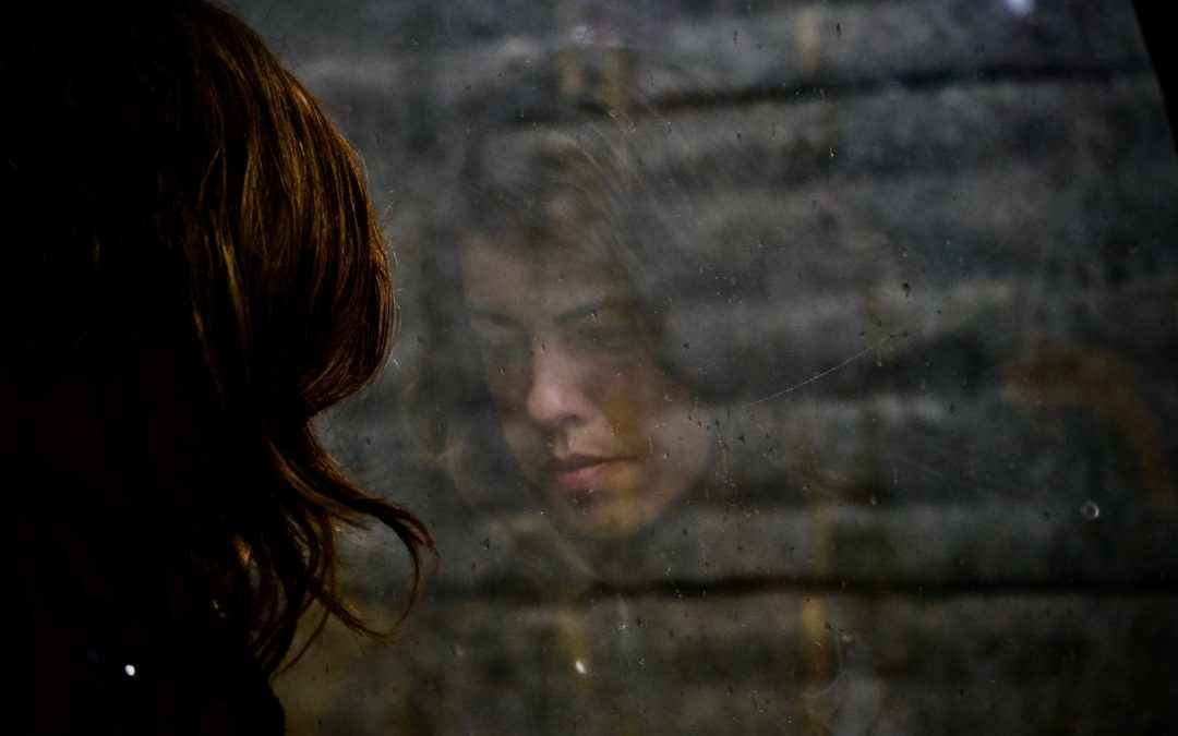 Woman with reflection of her sad face. This image represents the isolation and sadness that occurs in response to trauma & PTSD.