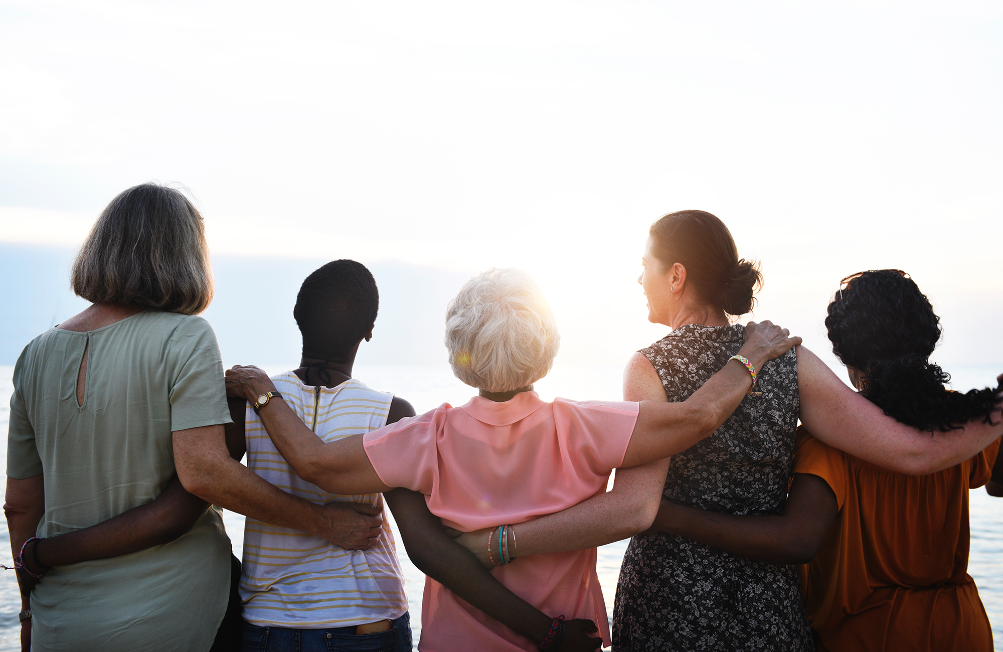 Image of women hugging with hands around each others backs, looking off at the sunset. This could represent a group of women who just completed therapy for women in Wilmington, NC. Reach out to a women's therapist today! | 28411 | 28412 |  28451