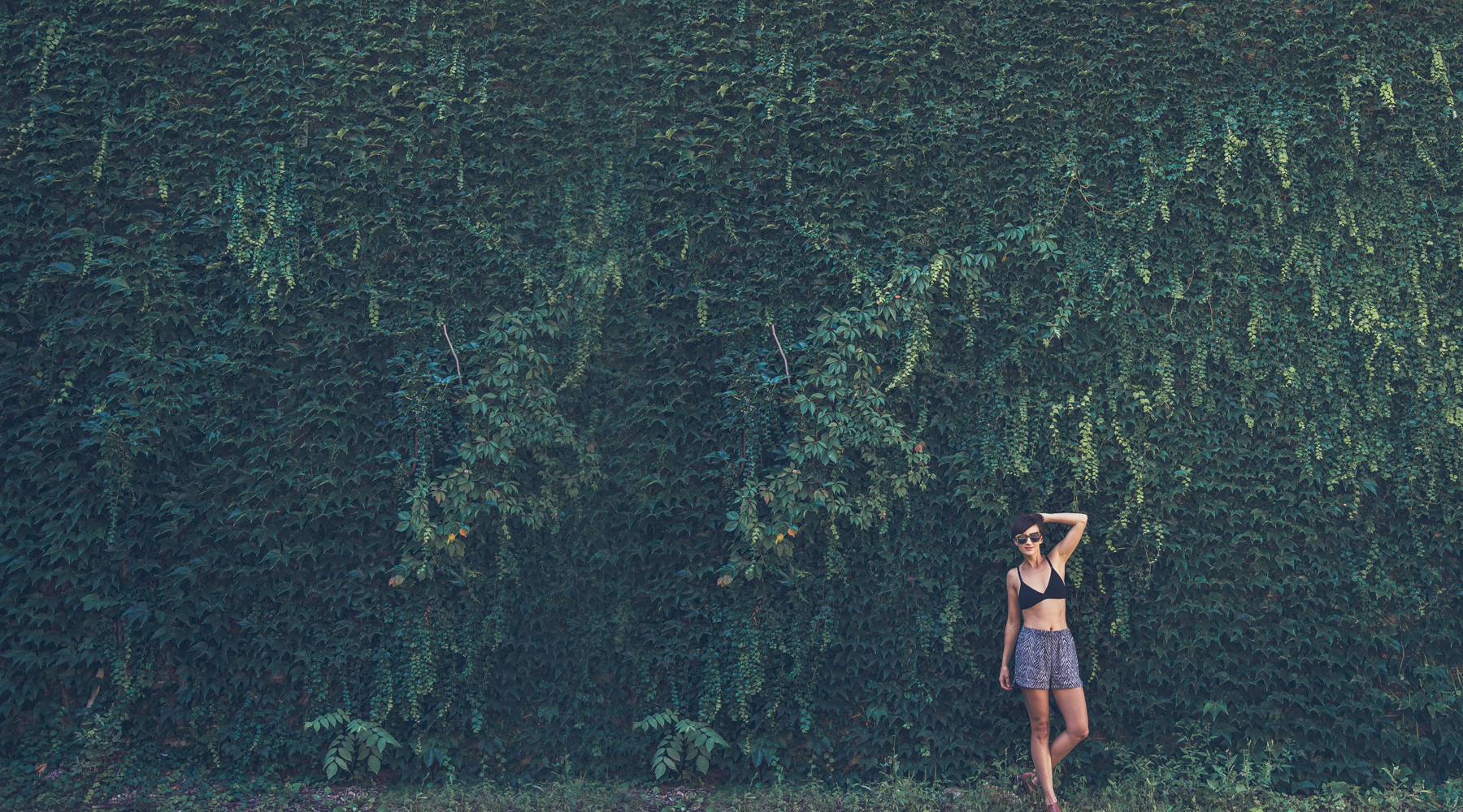 Photo of a woman in a swimsuit leaning against a wall covered in plants. This image illustrates the peace you can find when working on anxiety symptoms during anxiety treatment in Wilmington, NC. 28411 | 28412