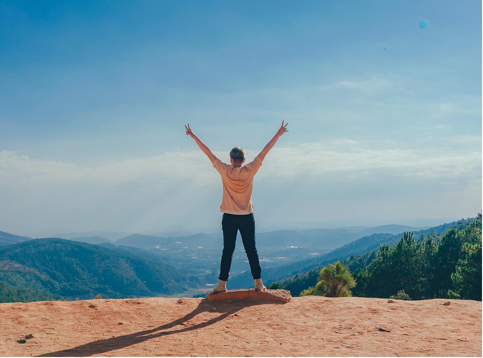 Image of a person on top of a mountain holding up two peace signs with their hands. This individual illustrates the confidence you can find after depression treatment in Wilmington, NC. 28401 | 28403