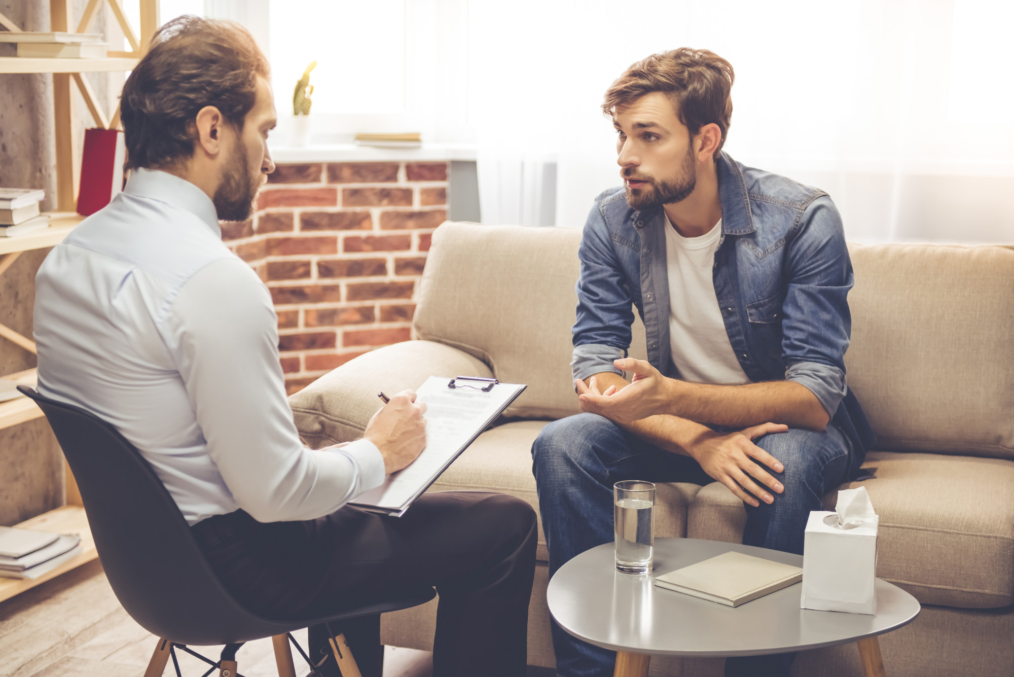 Image of a man sitting on a couch and speaking with a professional person. This image illustrates what meeting with an anxiety therapist in Wilmington, NC may look like. If you are struggling with anxiety symptoms in Wilmington, NC, reach out to us. | 28401 | 28403