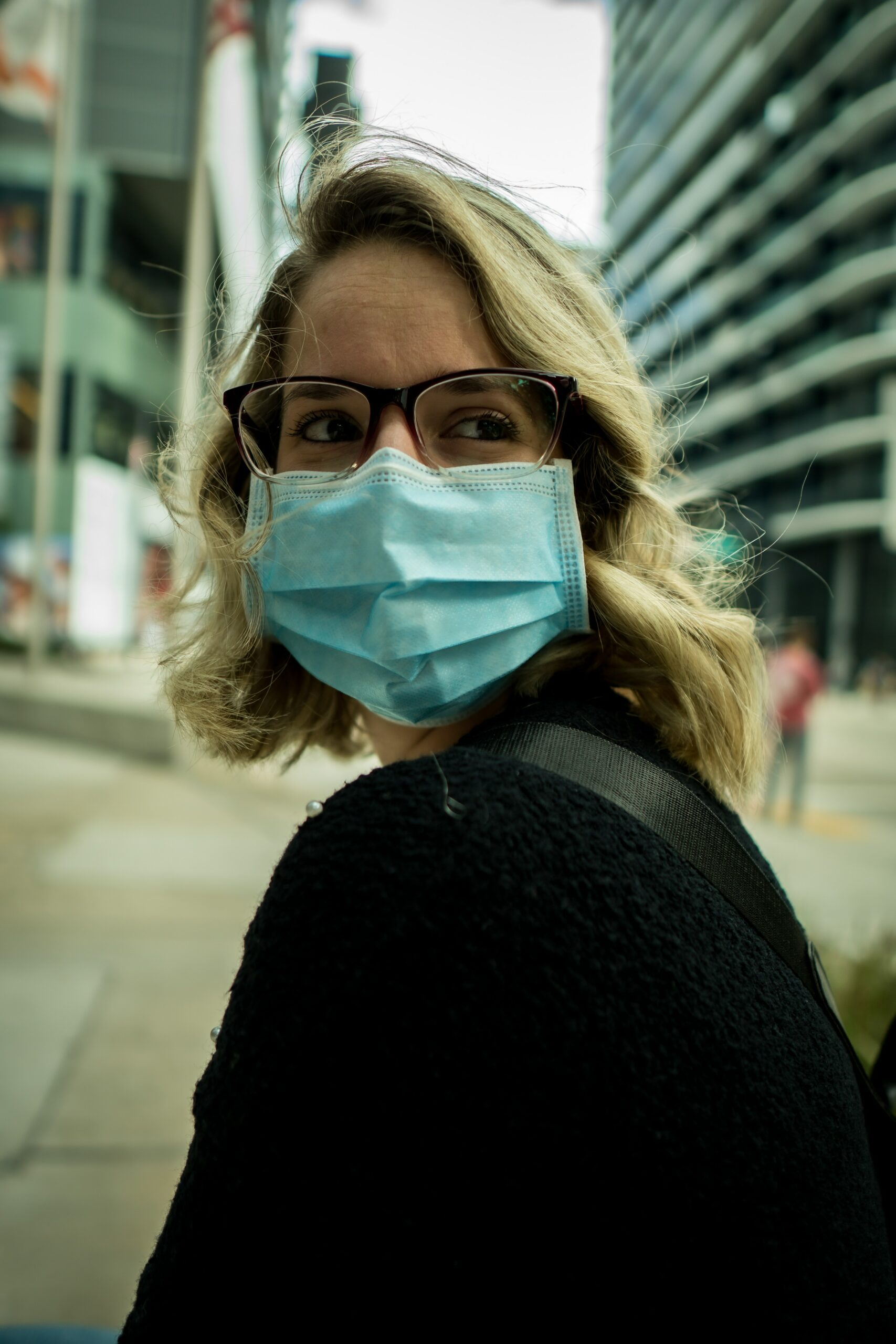 This image shows a woman wearing a mask outside in an urban area. This image represent the loneliness and COVID loss that occurred in 2020. Starting COVID counseling in Wilmington, NC can help. | 28405 | 28409