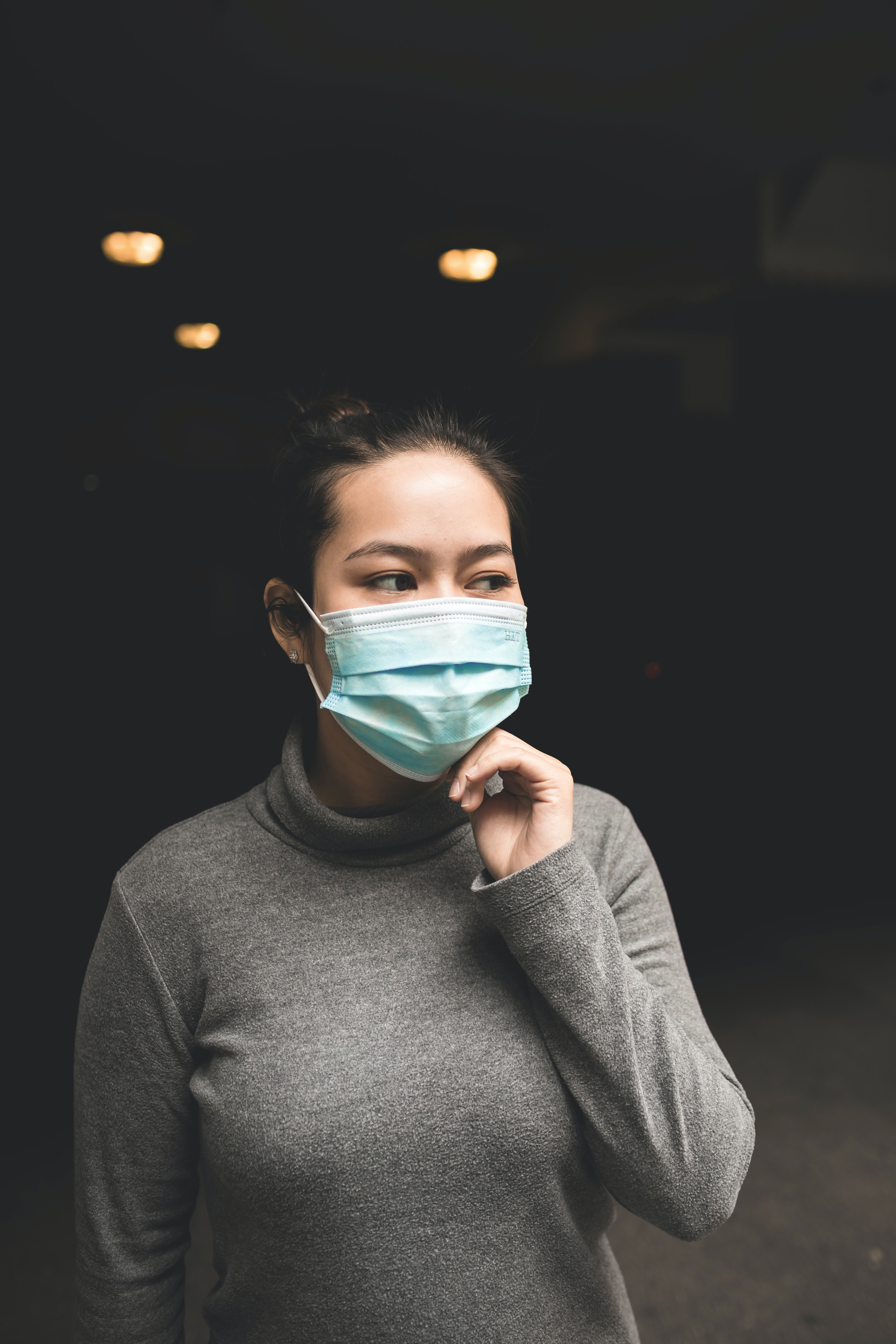 Image of a woman nervously touching her mask on her face. This image represents the impacts of the pandemic, including COVID loss. Get help from COVID counseling in Wilmington, NC. 28411 | 28412