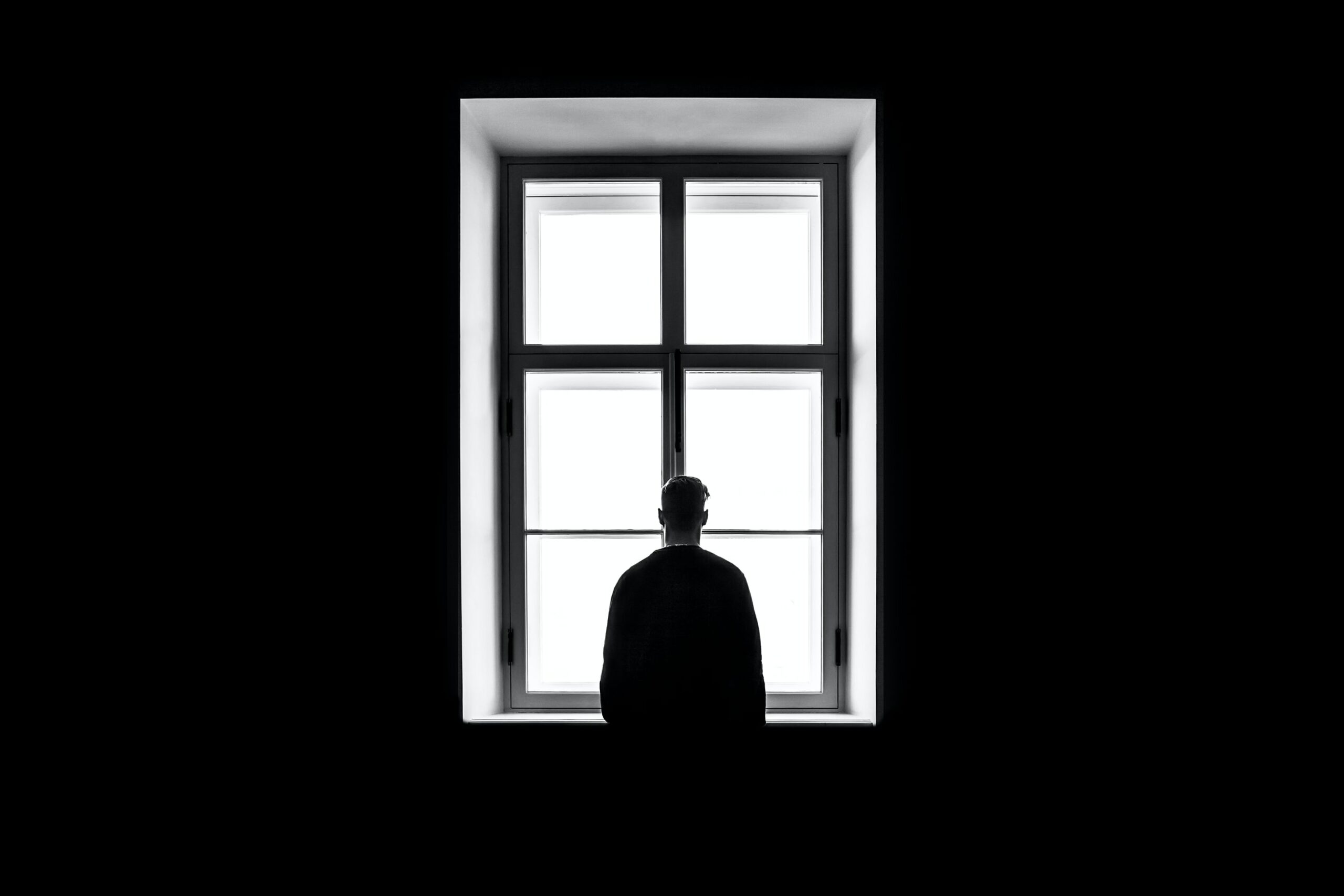 Black and white image of a man looking out a window. This image represents the isolation caused by the COVID-19 pandemic, which can be helped with COVID counseling in Wilmington, NC. 28401 | 28403